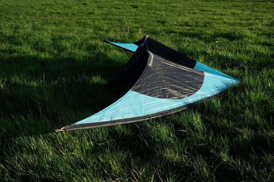 Cerf-volant bleu et noir dans l'herbe