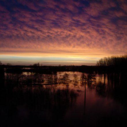 lever de soleil rose et violet se reflétant sur l'eau