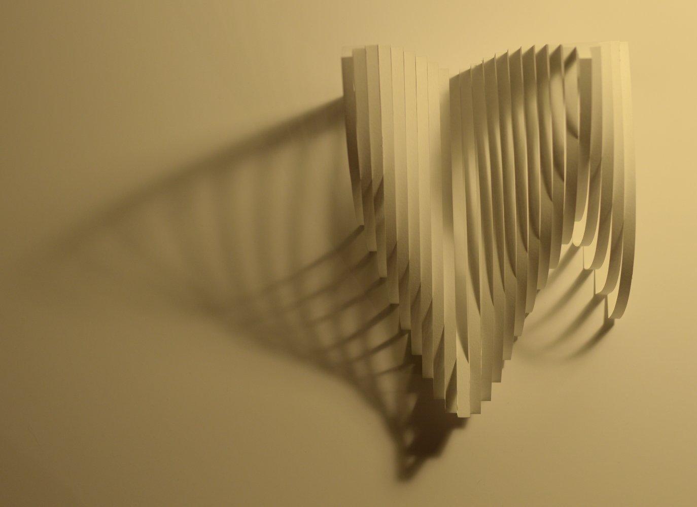 Pliages de bandes de papier vu de dessus avec l'ombre portée