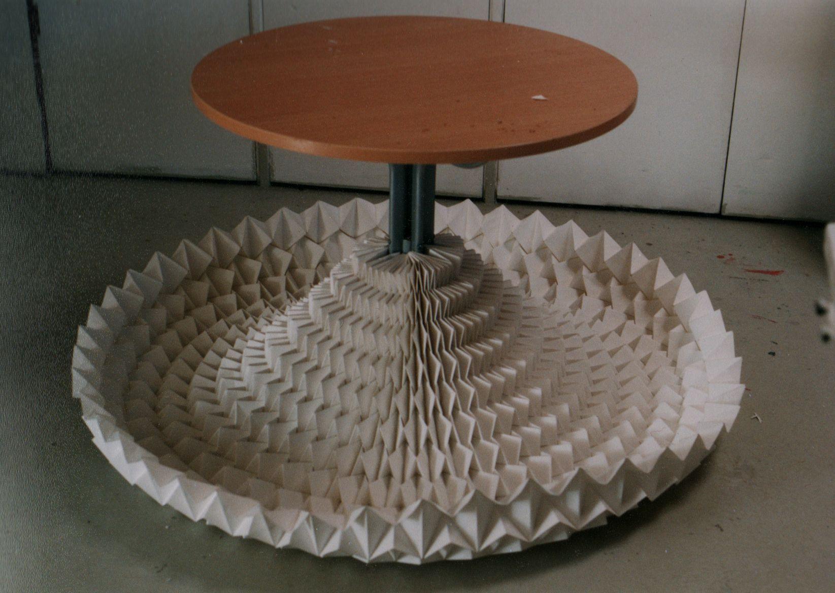 Le pied d'une table ronde s'évase en des milliers de plis