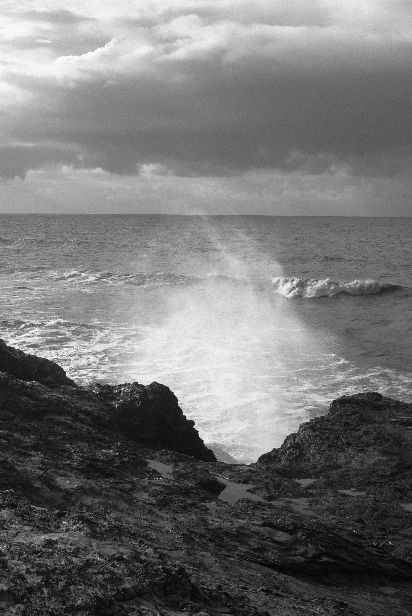 Photo noir et blanc d'une vague qui s'écrase sur des rochers