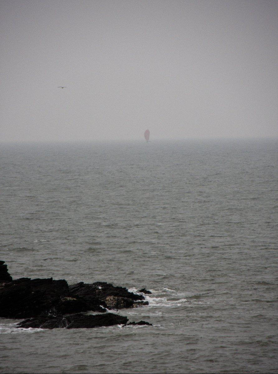une voile rouge au fond du brouillard