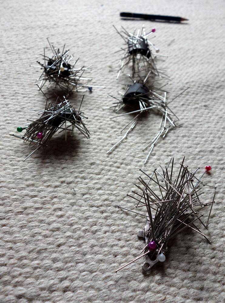 des épingles sont collées sur de aimants en formats de petites bêtes étranges.
